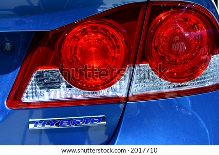 Lights of a car and the word Hybrid. - stock photo