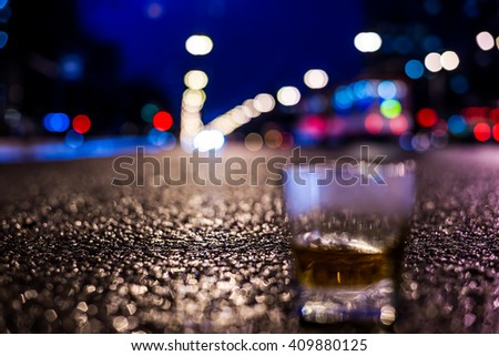 Lights of the city at night through the glass of alcohol, headlights of the approaching cars. View from the glass level with brandy standing on the asphalt, in blue tones - stock photo