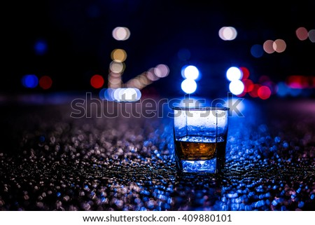 Lights of the city at night through the glass of alcohol, near the car rides. View from the glass level with brandy standing on the asphalt, in blue tones - stock photo