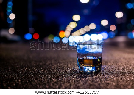 Lights of the city at night through the glass of alcohol, night avenue in the light of a passing car headlights. View from the glass level with brandy standing on the sidewalk, in blue tones - stock photo