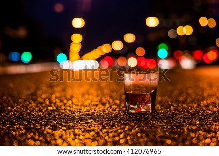 Lights of the city at night through the glass of alcohol, night ?venue in the light of car headlights. View from the glass level with brandy standing on the asphalt, focus on the asphalt - stock photo