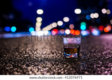 Lights of the city at night through the glass of alcohol, night ?venue in the light of car headlights. View from the glass level with brandy standing on asphalt, in blue tones, focus on the asphalt - stock photo