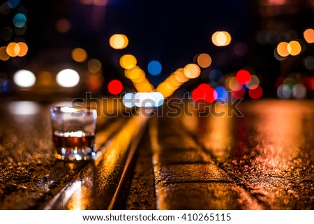 Lights of the city at night through the glass of alcohol, night ?venue with rails for trams and driving car. View from the level of the rails on which stands a glass of brandy - stock photo