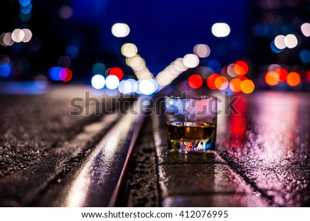 Lights of the city at night through the glass of alcohol, night ?venue with rails for trams. View from the level of the rails on which stands a glass of brandy, in blue tones, focus on the asphalt - stock photo