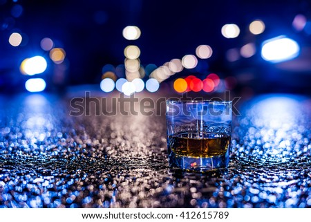 Lights of the city at night through the glass of alcohol, on the sides rushing cars. View from the glass level with brandy standing on the asphalt, in blue tones - stock photo