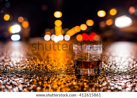 Lights of the city at night through the glass of alcohol, on the sides rushing cars. View from the glass level with brandy standing on the asphalt - stock photo