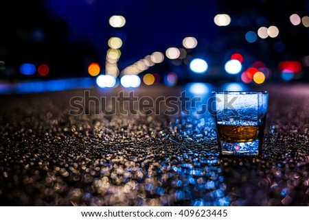 Lights of the city at night through the glass of alcohol, the car traveling along the avenue. View from the glass level with brandy standing on the asphalt, in blue tones - stock photo