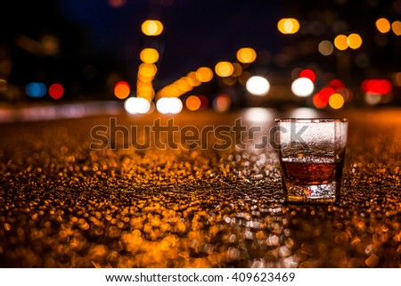 Lights of the city at night through the glass of alcohol, the car traveling along the avenue. View from the glass level with brandy standing on the asphalt - stock photo