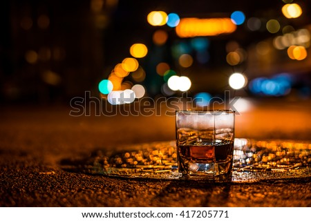 Lights of the city at night through the glass of alcohol, the night avenue with driving bus. View from the glass level with brandy standing on the wet manhole - stock photo