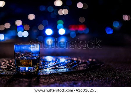 Lights of the city at night through the glass of alcohol, the night avenue with driving car. View from the glass level with brandy standing on the wet manhole, in blue tones - stock photo
