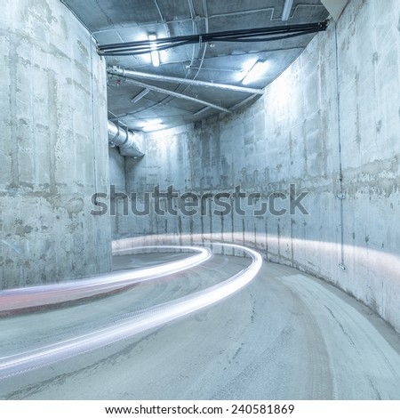 Lights of the moving car in the underground parking. - stock photo