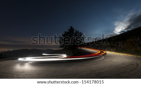 Lights on the asphalt, at night on a mountain road, illuminated by the moon begins to rise over the horizon, a car making a turn, leaving behind a trail of light. - stock photo
