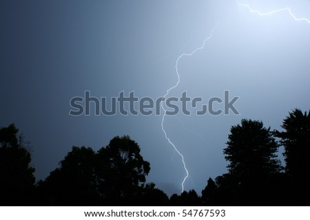 lightsning striking over trees during a night storm - stock photo