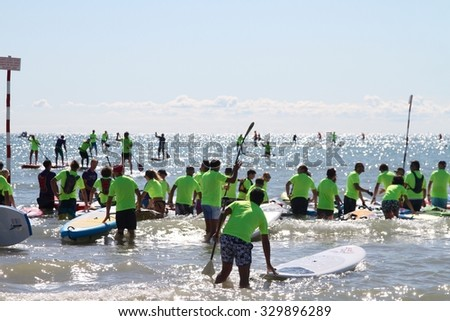LIGNANO, ITALY - september 6, 2015: SUP race. Stand up paddle surfing and boarding were born in Hawaii. The athletes maintain an upright stance on their boards using a paddle to race over the sea.  - stock photo
