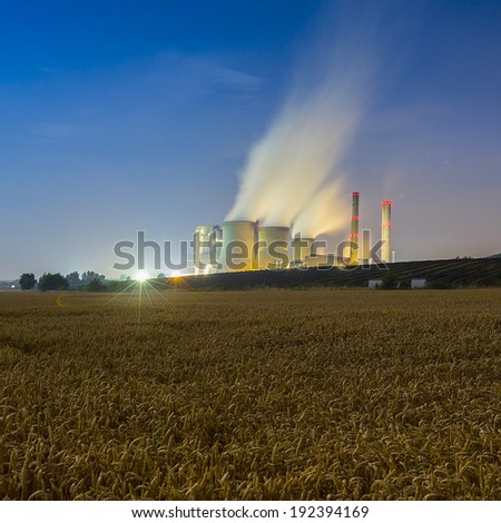 Lignite-fired power energy plant at night with cornfield in nrw weisweiler - stock photo