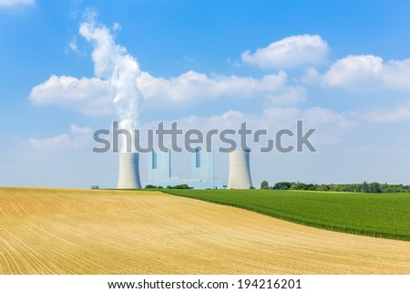 Lignite-fired power plant with cooling tower and agriculture landscape - stock photo