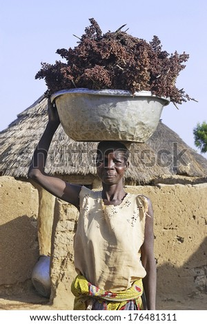 LIGUIDI MANGAM, BURKINA FASO - NOVEMBER 11 : portrait of a woman in her village carrying a load on the head, november 11, 2010 - stock photo