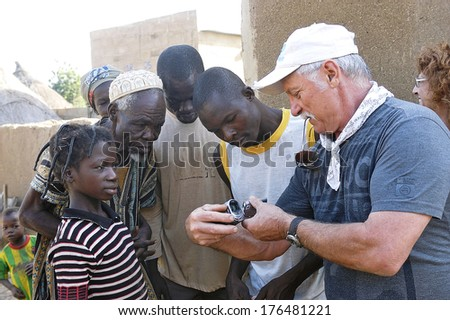 LIGUIDI MANGAM, BURKINA FASO - NOVEMBER 11 : Sharing a French tourist watching her videos with the inhabitants of a village in Burkina Faso which he visited, november 11, 2010 - stock photo