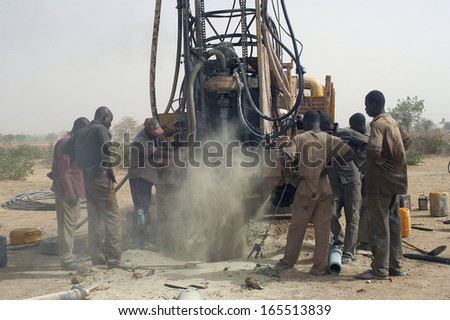 LIGUIDIMALGEM,  BURKINA FASO - FEBRUARY 24: In Africa the water is underground, the worker drill a well using a very old drill and breathes a fine dust, February 24, 2007 - stock photo