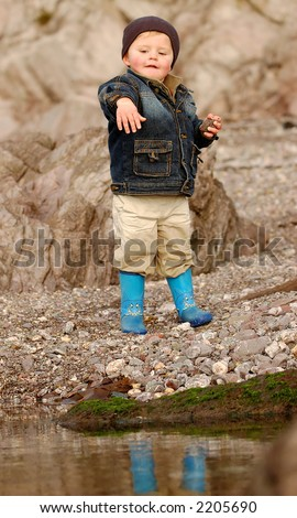 liitle boy throwing stones in a rock pool on a beach - stock photo