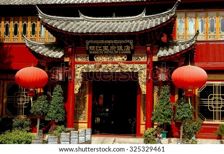 Lijiang, China - April 21, 2006:  Entrance doorway with carved gilded dragons, flying eave tiled roofs, and large Chinese lanterns at the distinguished Wang Fu Hotel of Lijiang