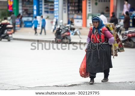 Lijiang, China - Jun 21, 2015: : Woman picking up trash in Lijiang ancient town in China on Jun 21, 2015, Lijiang is one of the most beautiful cities of China with a rich culture and history.