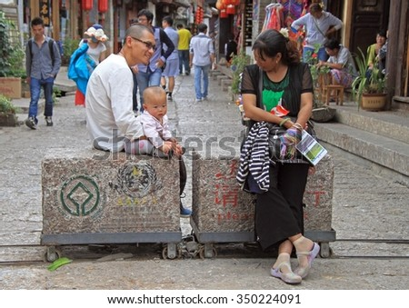 LIJIANG, CHINA - JUNE 10, 2015: people are communicating on the street in Lijiang, China