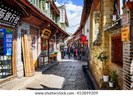 LIJIANG, YUNNAN PROVINCE, CHINA - OCTOBER 23, 2015: Asian tourists are walking in the Old Town of Lijiang. Scenic view of ancient street on a sunny day. Lijiang is a popular tourist destination.