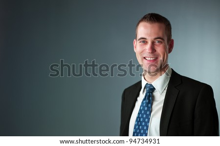 likable young businessman smiles into camera