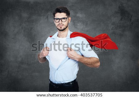 Like a superhero. Confident young man with superhero cape taking of his shirt and looking at camera while stabnding against concrete wall   - stock photo