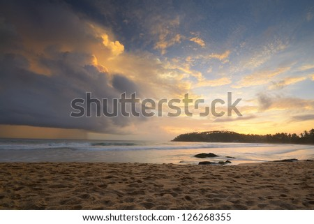 Like an atomic explosion, clouds gathering at the horizon at the tropical beach of Mirissa, Sri Lanka. Double exposure shot taken at dusk during monsoon season. - stock photo