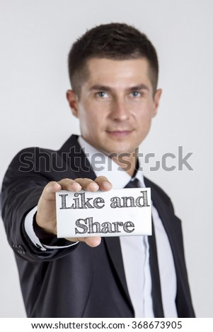 Like and Share - Young businessman holding a white card with text - vertical image