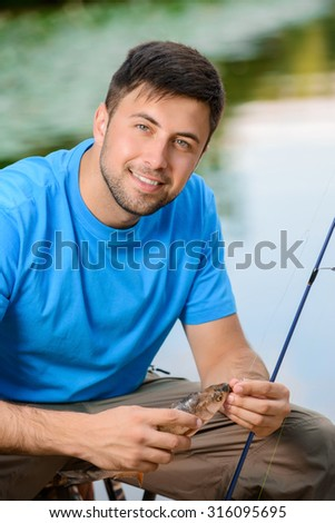 Like fishing. Pleasant contented smiling man holding fish and rod while expressing positivity - stock photo