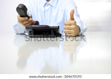 like hand with office phone on desk - stock photo