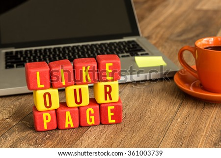 Like Our Page written on a wooden cube in a office desk - stock photo