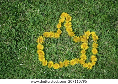 Like symbol made from yellow flowers on a green grass background  - stock photo