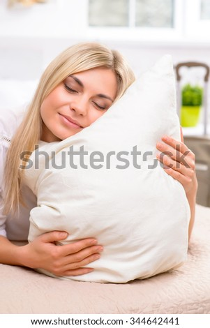 Like this pillow. Young attractive woman presses her cheek against a pillow and enjoying the moment - stock photo