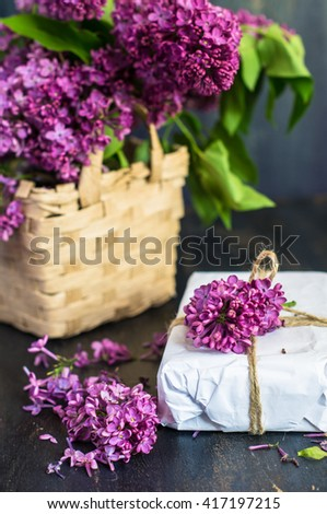 Lilac Bouquet and gift box on rustic wooden background - stock photo