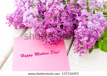 Lilac bouquet with Happy Mothers Day card  on wooden table - stock photo