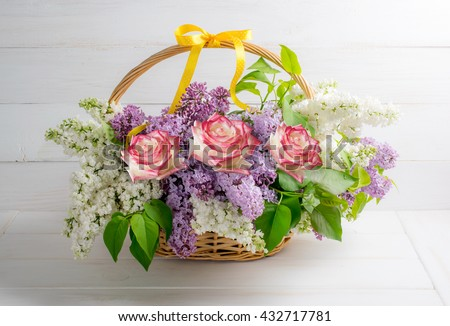 Lilac bouquet with roses in basket on background of shabby wooden planks in rustic style