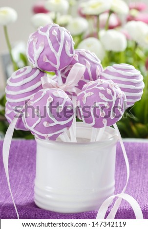 Lilac cake pops in white ceramic jar. White and pink daisies in the background. Party table setting. - stock photo