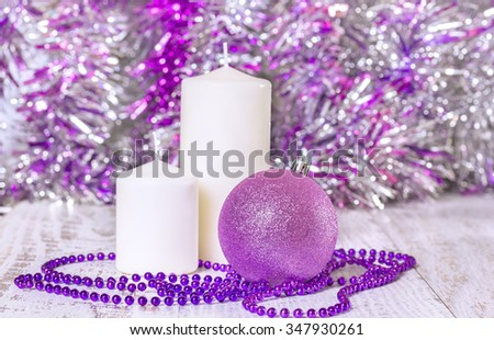 Lilac Christmas ball, beads and two white candles on wooden boards on a blurred background of tinsel. Selective focus - stock photo