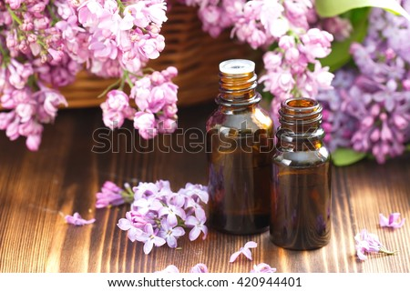 Lilac essential aroma oil and fresh flowers - stock photo