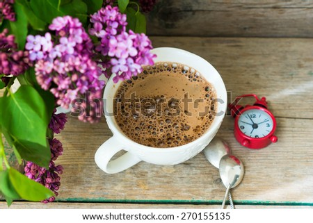 lilac flowers in a pot and Cup of cappucino on wooden table - stock photo