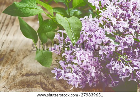 Lilac flowers on vintage wooden table, selective focus - stock photo