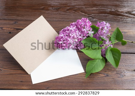 Lilac flowers with white paper on wooden table. - stock photo