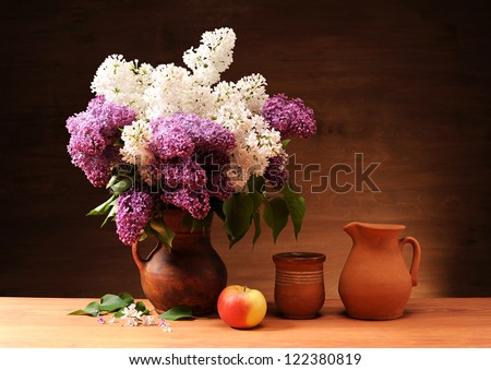 Lilac in a ceramic vase and apples