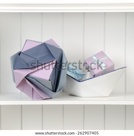 lilac Kusudama ball on a white shelf with gift box in a ceramic boat origami - stock photo