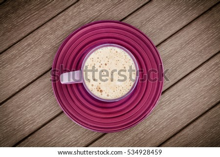 Lilac mug with hot cappuccino on wooden background