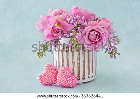Lilacs and pink roses flowers decorated with a heart on a blue background with texture . Floral gift for a wedding or birthday.